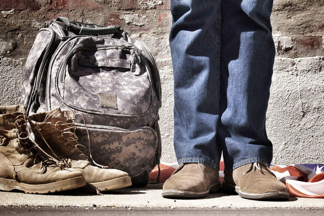 Person standing next to military bag and boots.